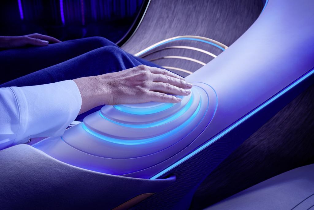 Die Passagiere sind mit ihrem ergonomischen Fahrzeug über die Sinne verschmolzen und können verschiedene intuitive Funktionen über Projektionen auf der Handfläche nutzen. Passengers are fused across the senses with their ergonomic vehicle and can use various intuitive functions via projections on the palm of their hands.